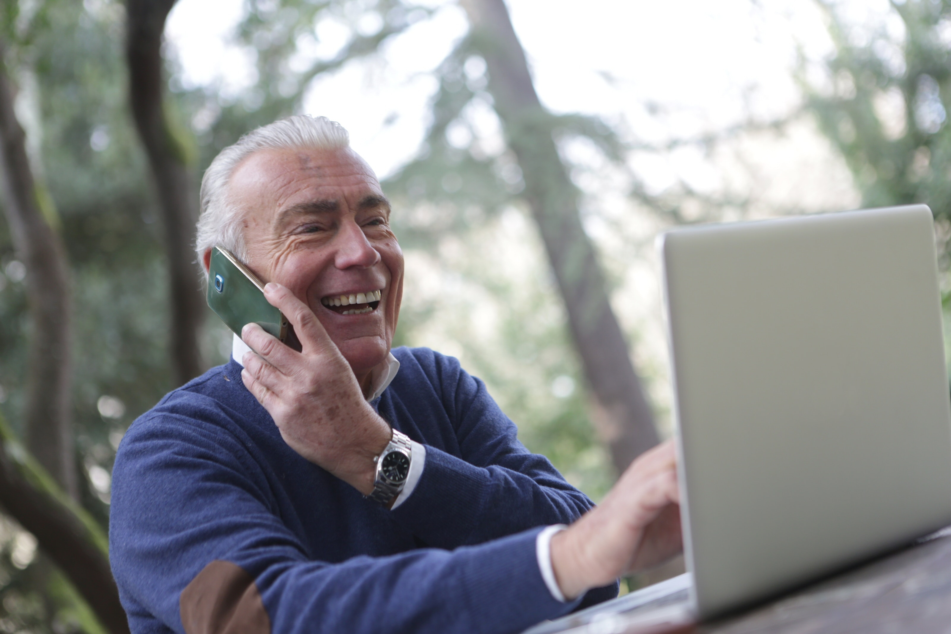 elderly man on phone and laptop receiving remote elder law services