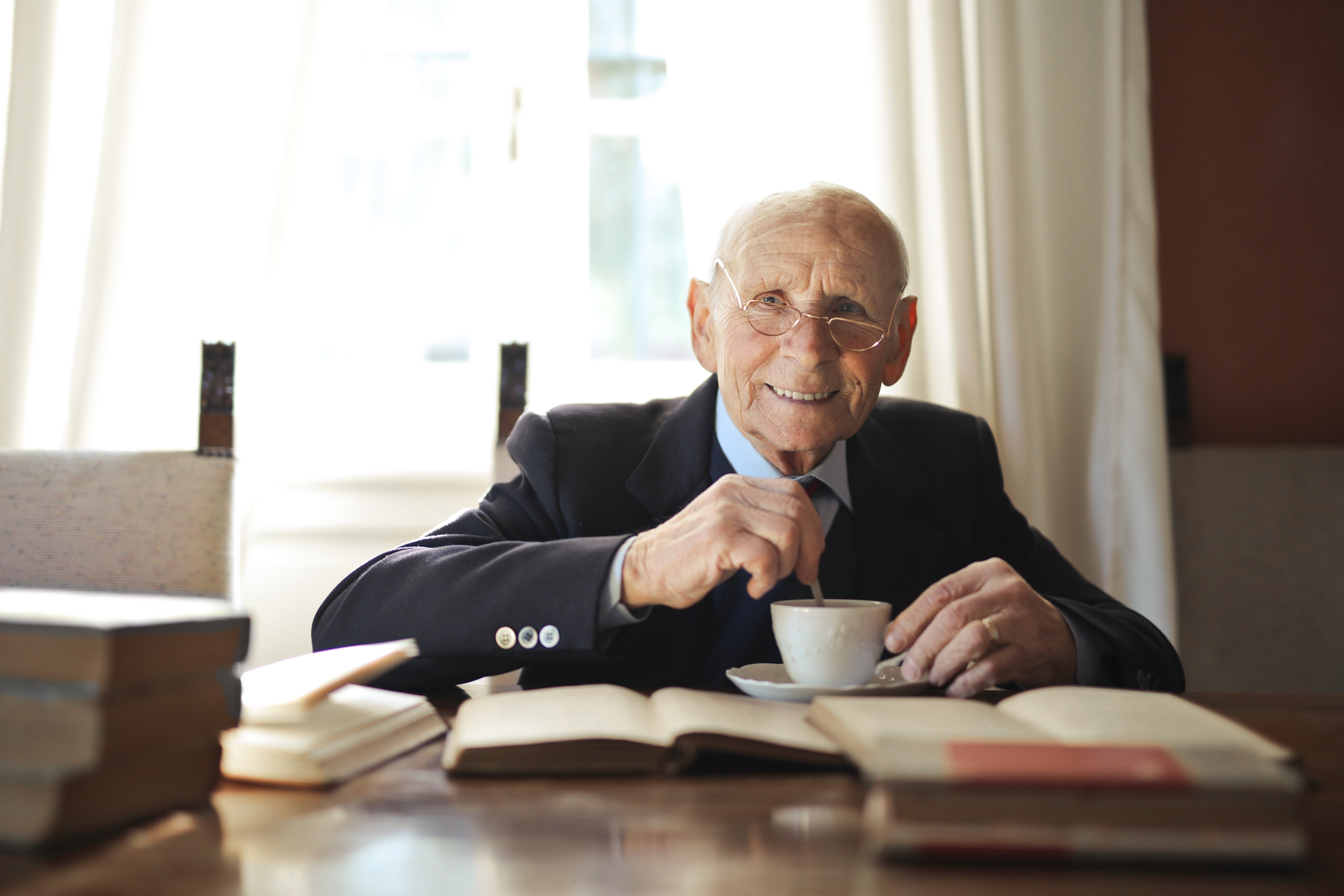 senior man enjoying a book and a cup of coffee