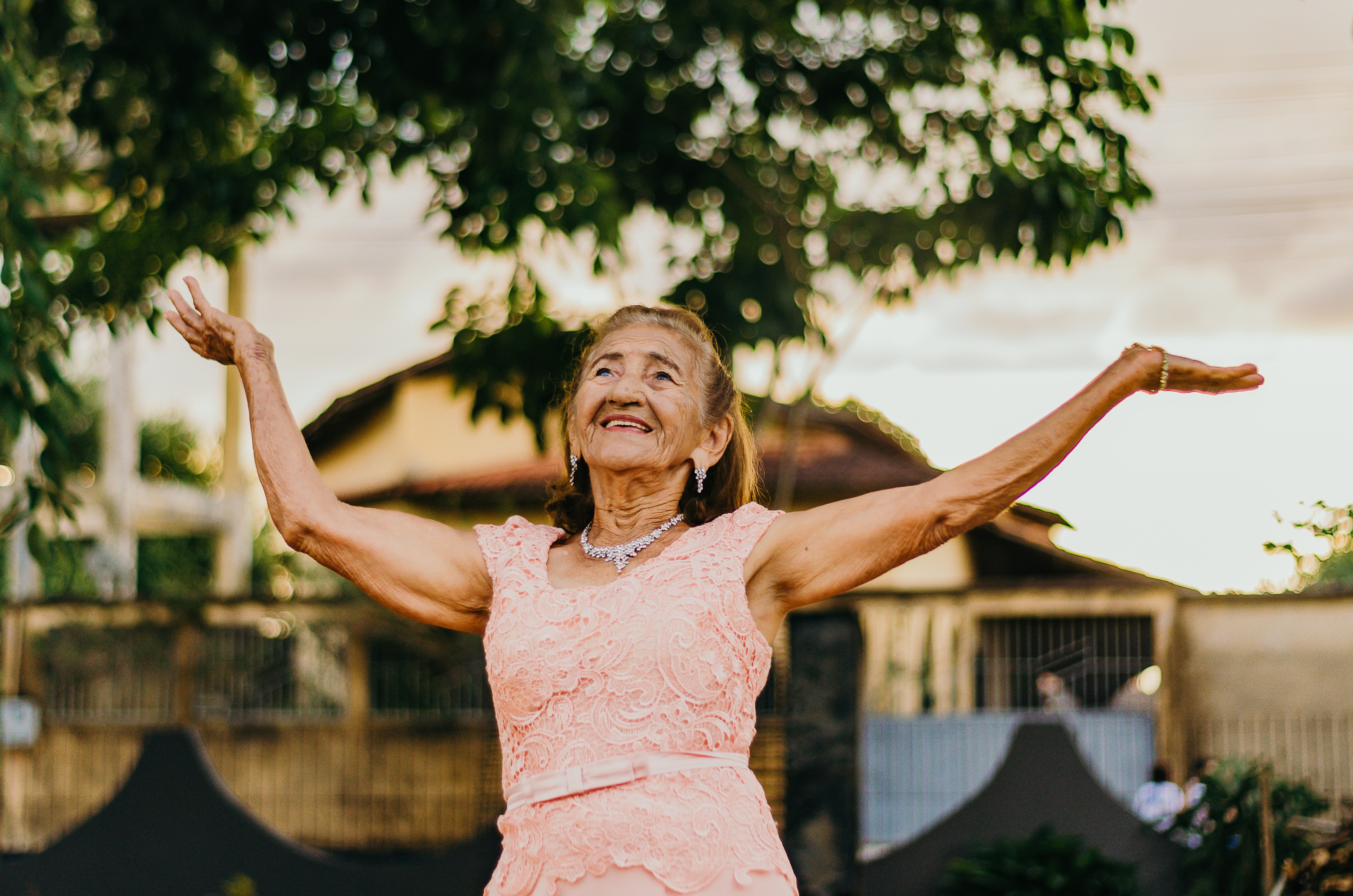 elderly woman smiling and raising her hands to the sky