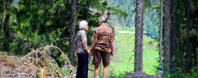 elderly couple holding hands in the woods