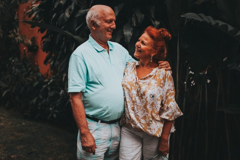 elderly couple smiling with arms around each other outside