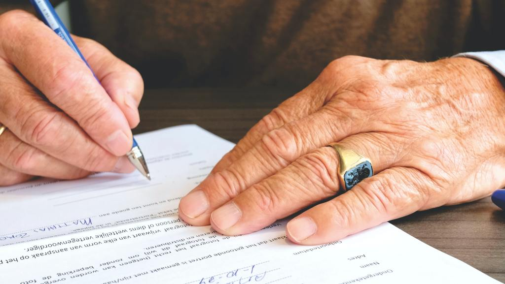 elderly man signing a power of attorney legal document