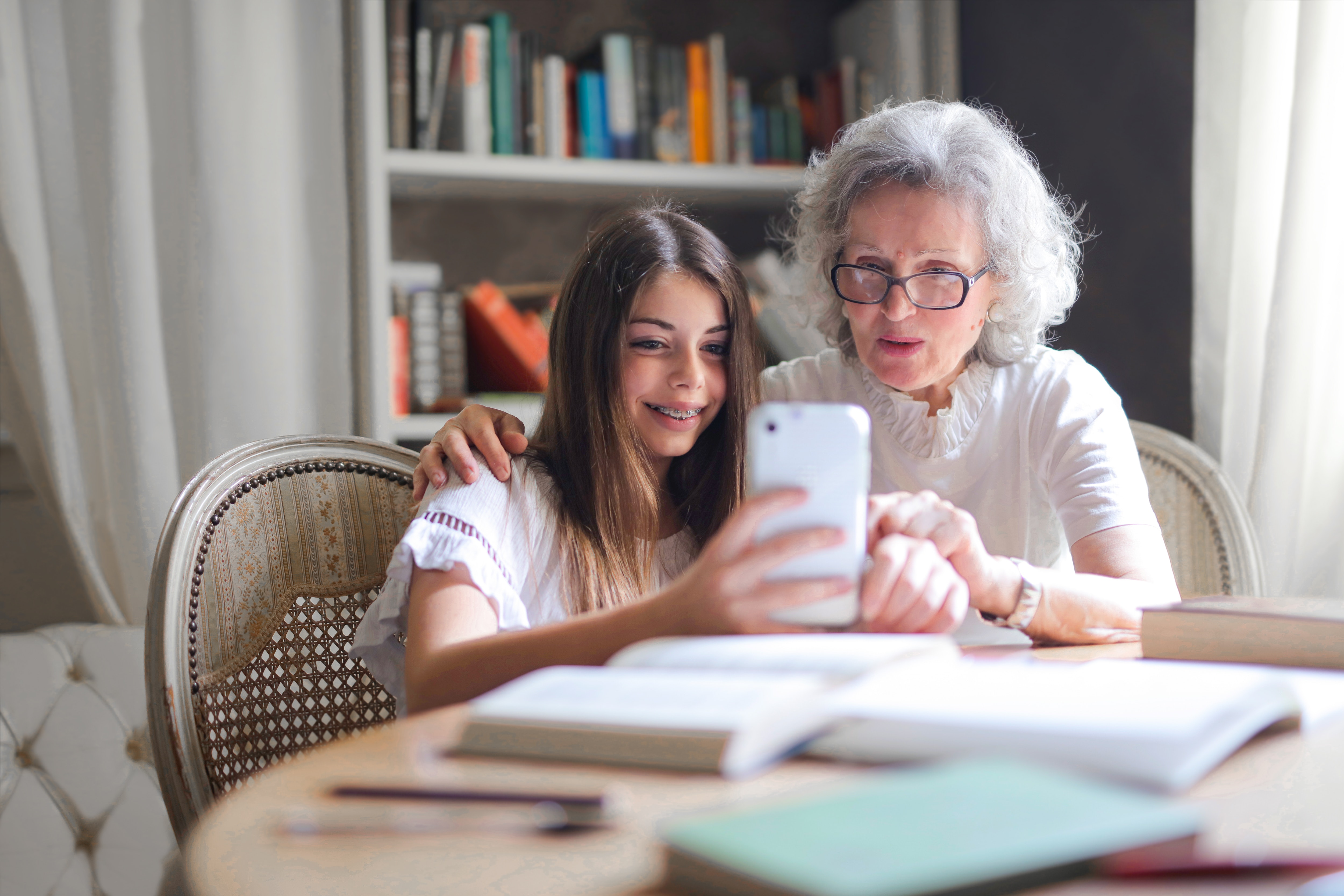 smiling grandchild with grandmother looking at phone