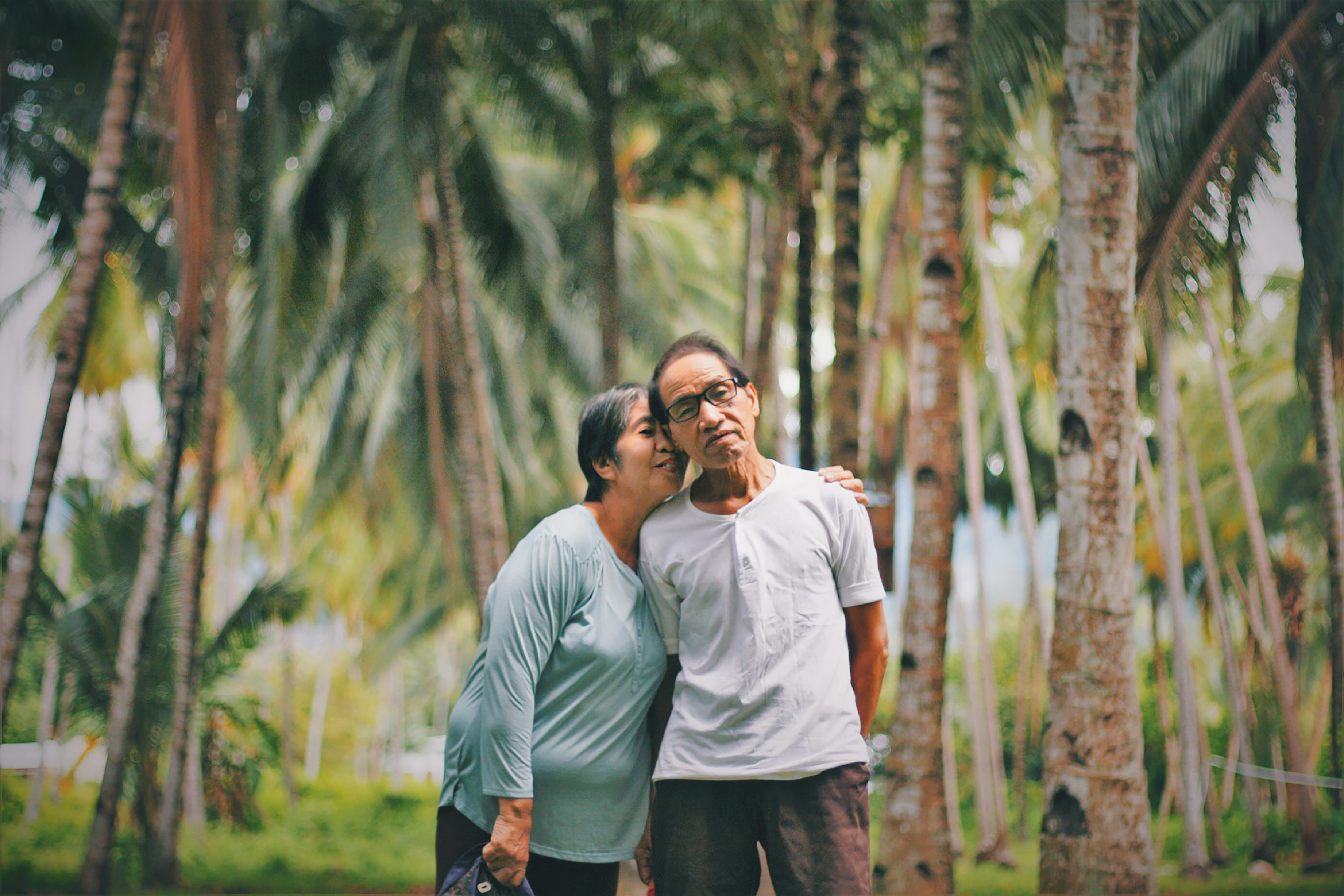 elderly woman putting arm around husband standing among tropical trees