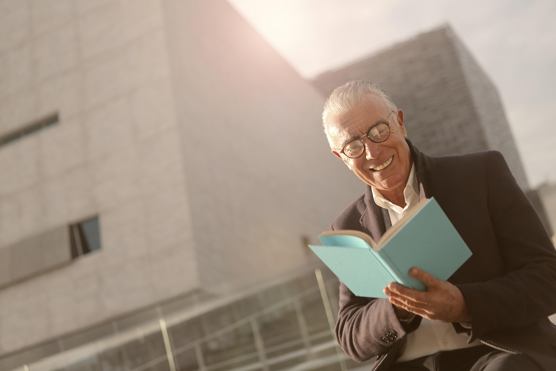 smiling elderly man reading outside