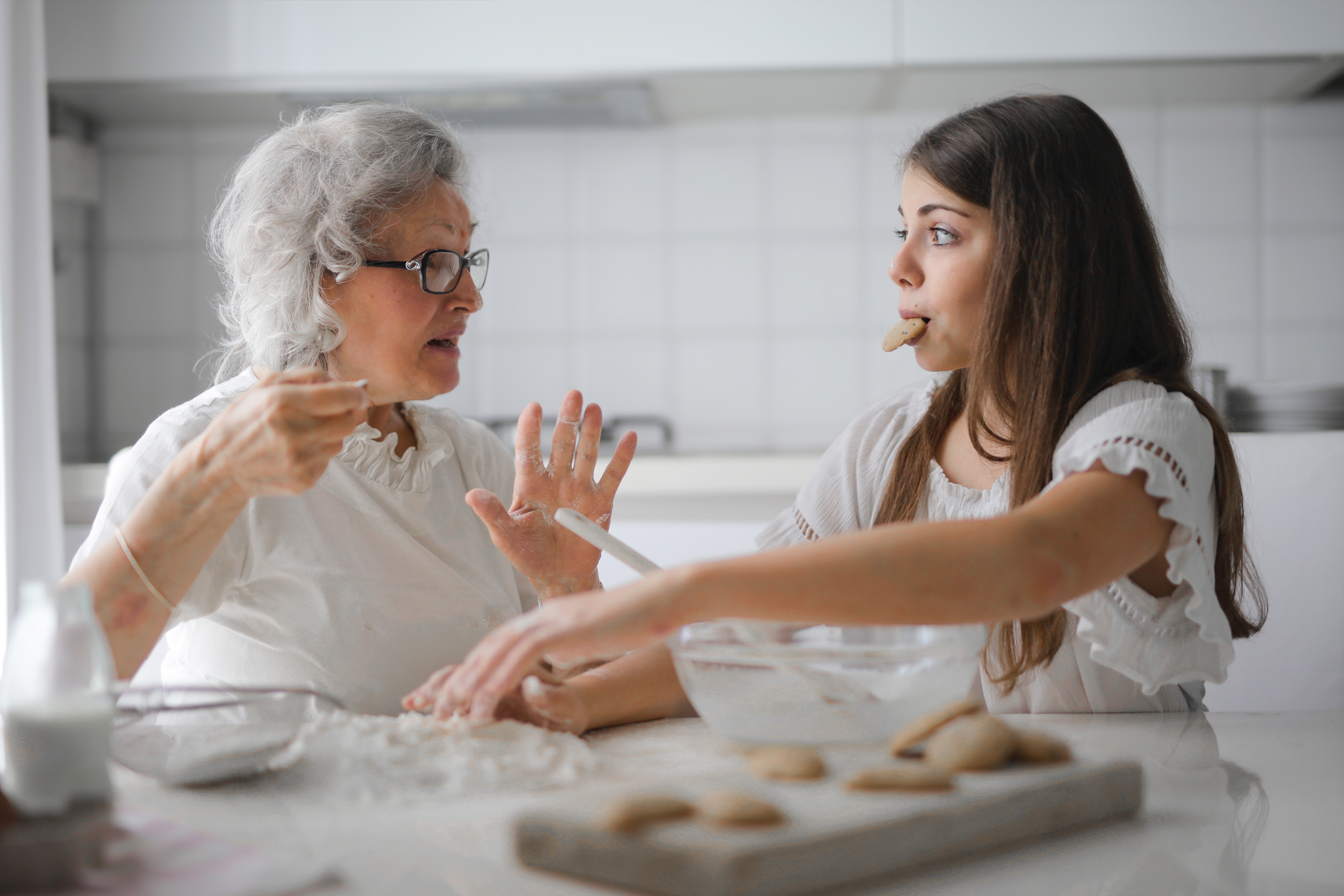 grandmother with granddaughter eating in kitchen