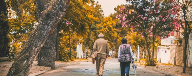senior couple walking along street with trees