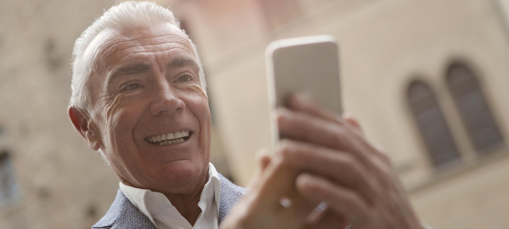elderly man reading information on cell phone