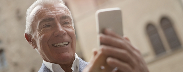 elderly man reading information on cell phone