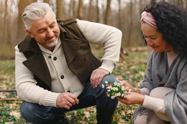 senior couple picking flowers among trees