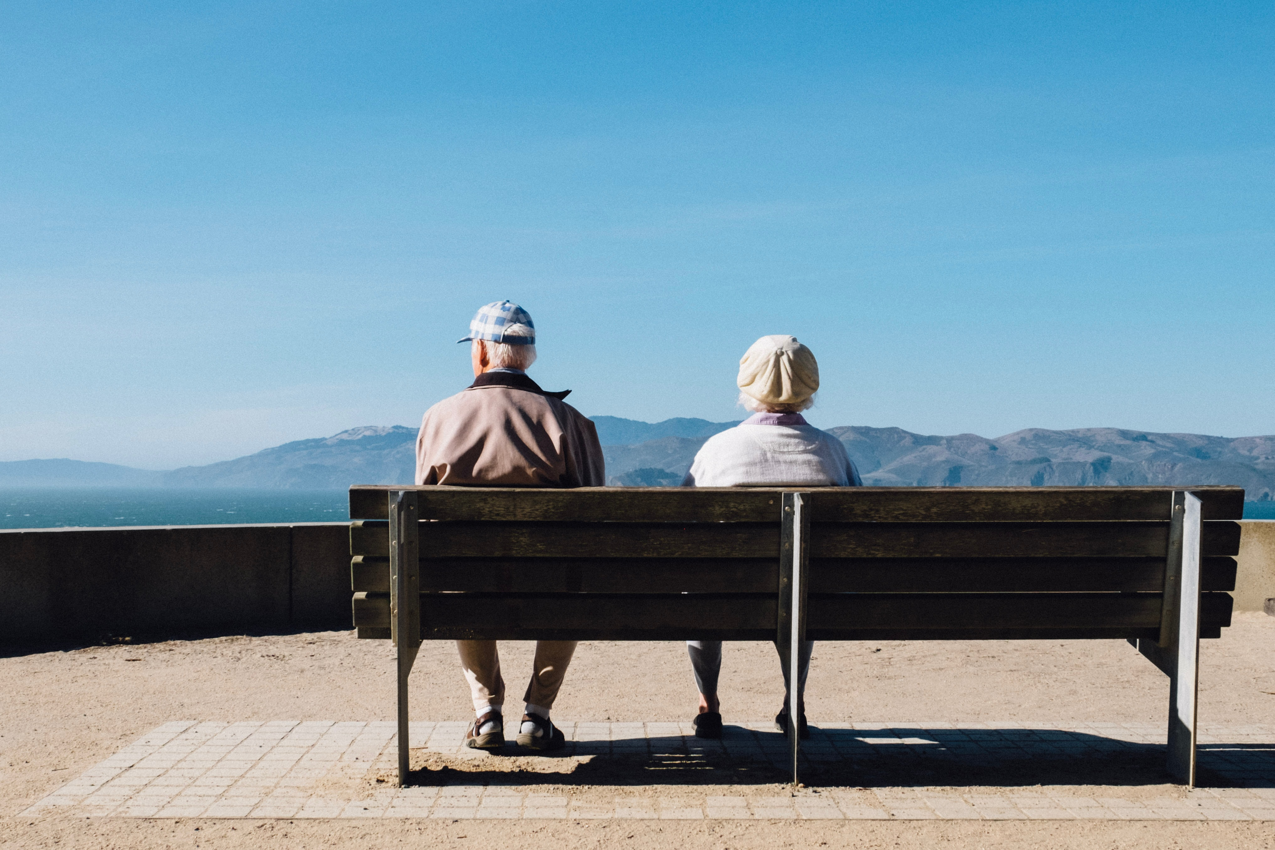 elderly couple sitting on bench with mountain view