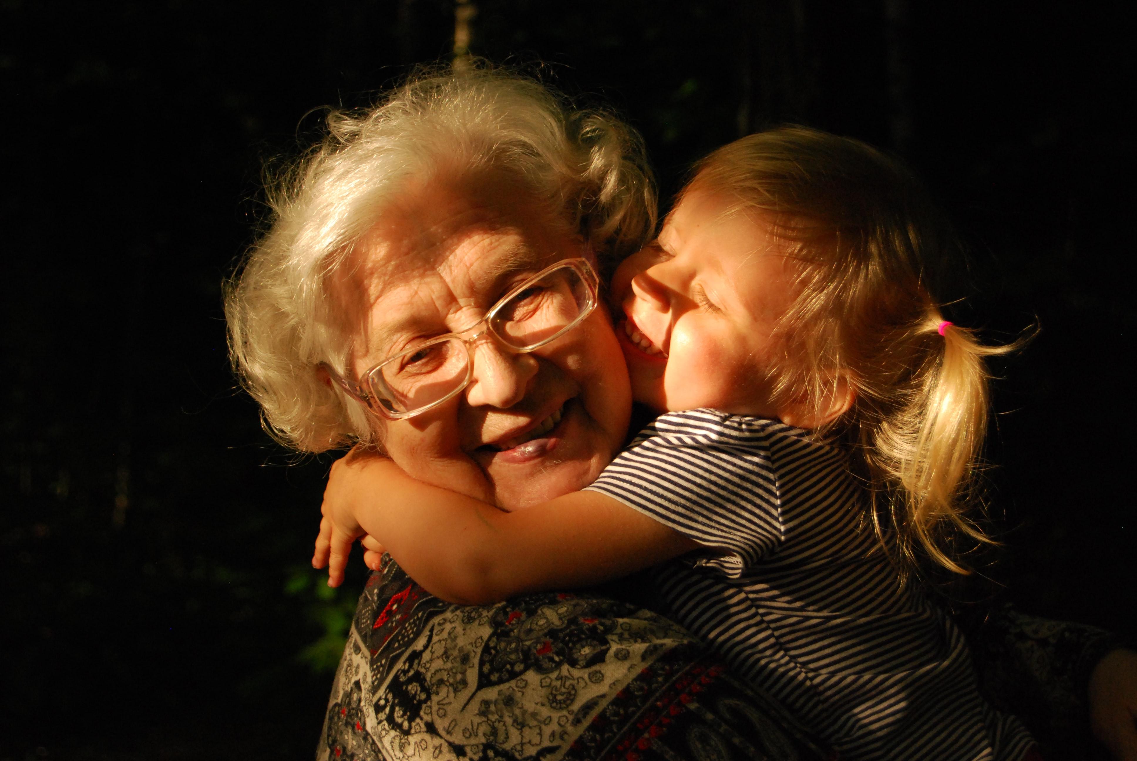 granddaughter hugging grandmother smiling