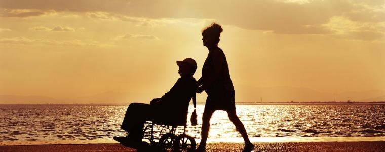 woman pushing husband in wheelchair
